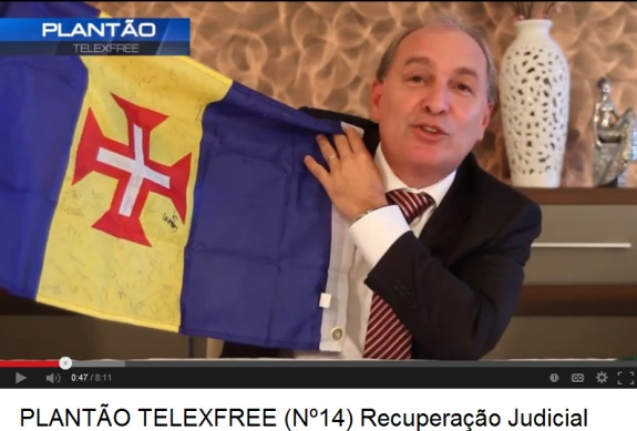 Carlos Costa displays the flag of Medeira while announcing TelexFree is seeking bankruptcy protection.